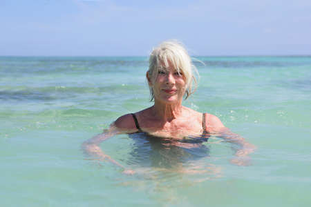 Senior woman swimming in the sea photo