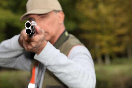 A hunter aiming his rifle photo