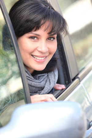 Young woman leaning out of the window of a car photo