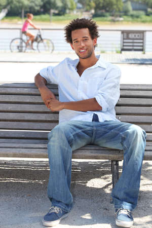 sitting on a bench: young man sitting on a bench