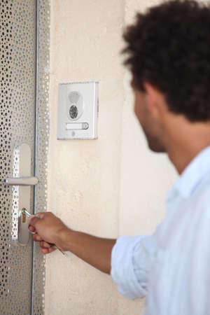 security door: Man opening door with key