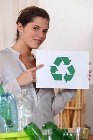 reprocess: Woman recycling glass and plastic bottles