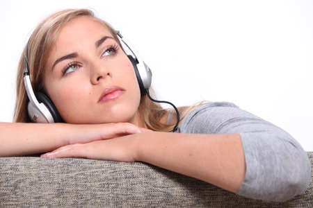 A young woman listening to music on a sofa  photo