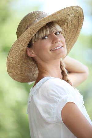 Portrait of blond woman outdoors wearing straw hat photo