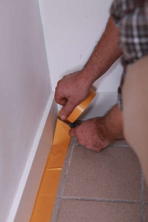 skirting: Man sticking tape to skirting board