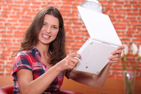 Angry woman holding a laptop photo