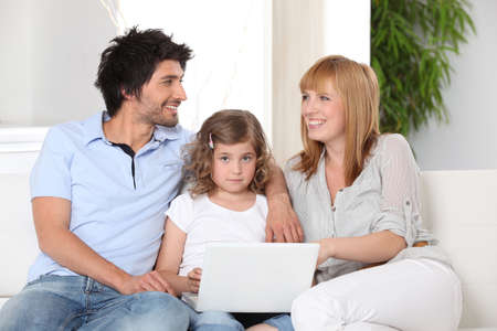 demografia: Padres e hija usando un ordenador portátil