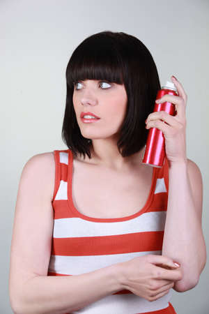 unpleasant smell: Woman holding deodorant, studio shot Stock Photo