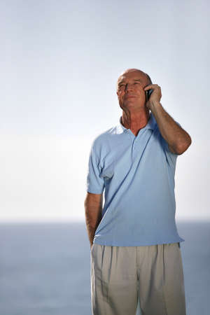 Older man taking a call by the sea photo