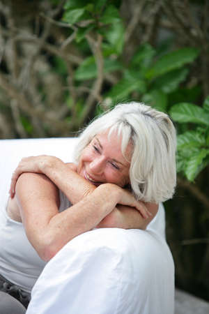 grey haired: Grey haired woman relaxing on a garden sofa