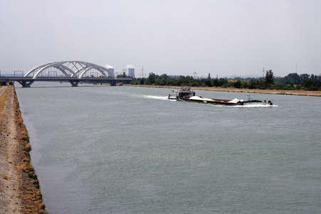 fluvial: Barge navigating a river Stock Photo