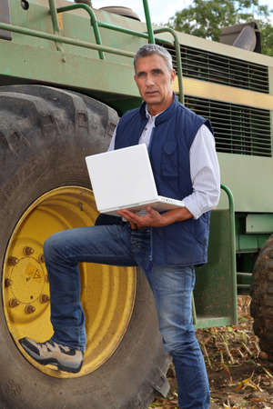 Farmer standing next to his large John Deere tractor with a laptop computer Stock Photo