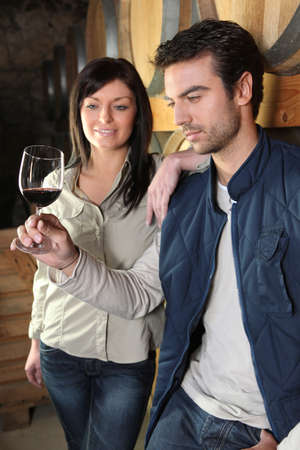 Couple tasting wine in cellar photo