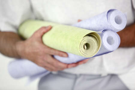 jumpsuite: a handyman holding tapestry rolls