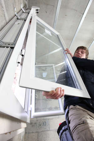 glass door: Man fitting a window Stock Photo