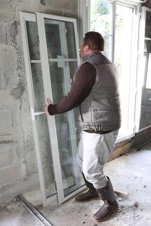 installing: Man installing new windows Stock Photo
