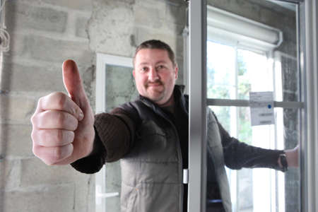 Man fitting a window giving you the thumbs up Stock Photo