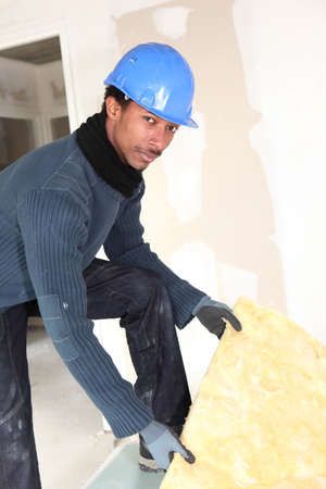 efficiently: Construction worker insulating wall Stock Photo