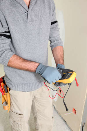 hz: Electrician using multimeter Stock Photo