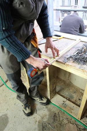 carpenter vise: Manual worker marking plank of wood Stock Photo