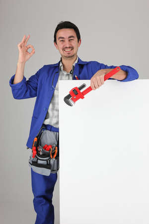 Tradesman giving the a-ok sign and standing behind a blank sign Stock Photo