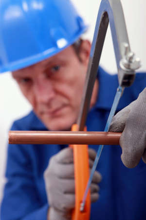 fittings: Man sawing copper pipe