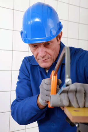 Manual worker cutting length of pipe photo