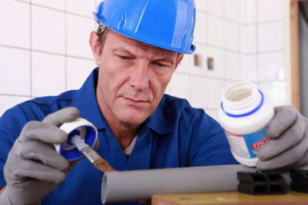 Plumber carefully gluing plastic pipe photo
