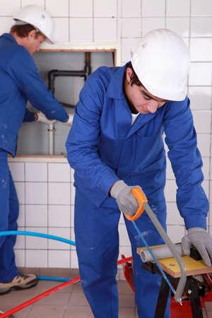 white work: Two plumbers hard at work Stock Photo