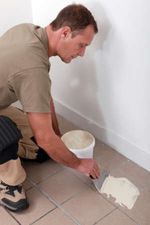 Man preparing to retile a floor Stock Photo - 22868606