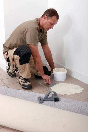 tile adhesive: Carpet fitter spreading adhesive on a tiled floor