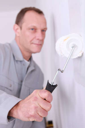 Man using a roller to paint a room white photo