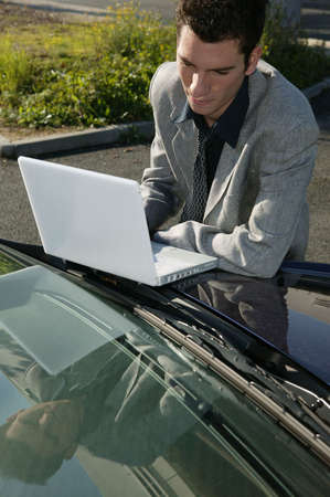 Businessman resting a laptop on his car bonnet photo