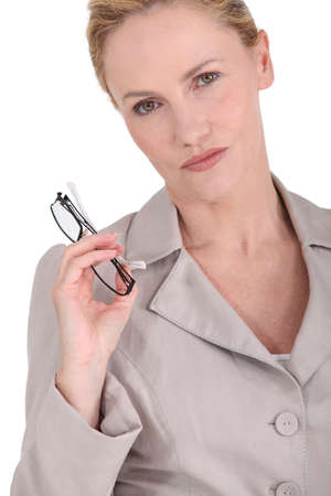 forbidding: Strict woman holding eyeglasses Stock Photo