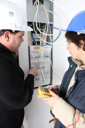 fuse box: Two electricians repairing fuse box