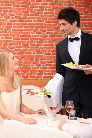 Waiter serving food to customer photo