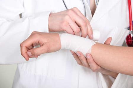 cut wrist: Doctor putting bandage on wrist Stock Photo
