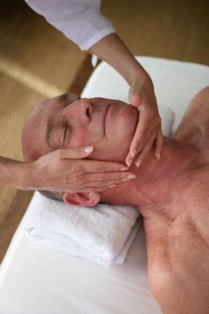 sensual massage: Elderly man receiving a head massage Stock Photo