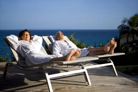 loungers: Senior couple on sun lounger whilst on holiday