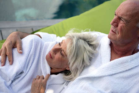 Middle-aged couple relaxing on decking Stock Photo - 22868999