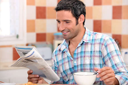 informed: Black man having breakfast with newspaper Stock Photo