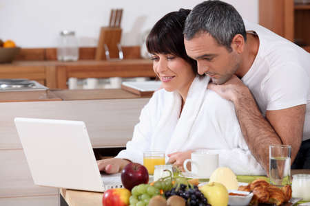 Couple eating breakfast together whilst browsing the internet photo