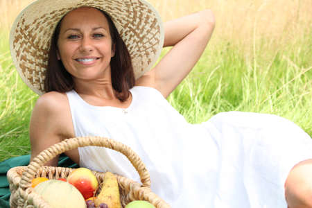 downtime: Woman lying in a field with a basket of fruit