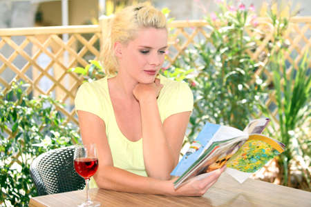 Woman reading with a glass of wine photo