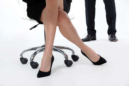 Businesswoman in high heels sitting in a swivel chair photo