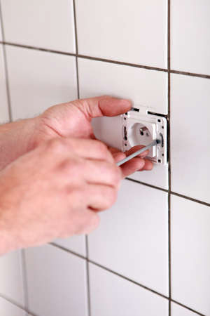 Handyman fixing electrical socket photo