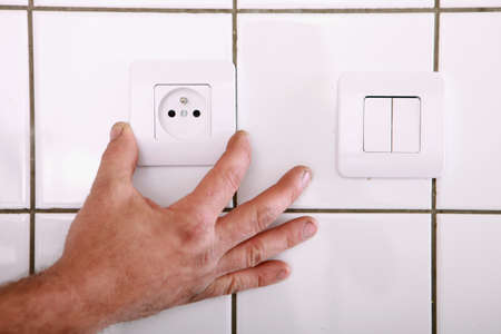 Man fitting a continental wall socket photo