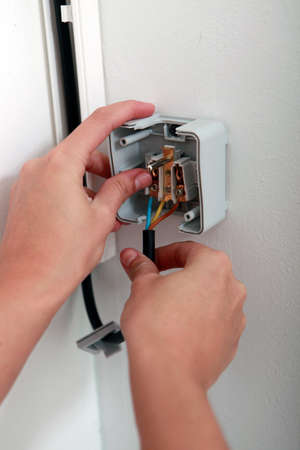 Electrician repairing wall socket photo