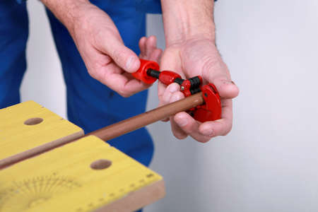 plumbing accessories: Plumber using a pipe cutter