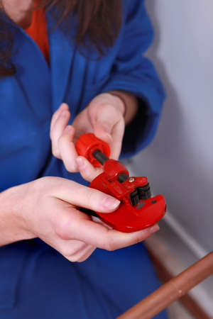 Female plumber with a pipe cutter photo